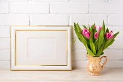 El oro adornó la maqueta del marco del paisaje con los tulipanes rosados brillantes adentro Fotos de archivo