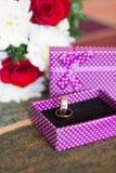 El oro anillo de bodas en una caja con un fondo del ramo foto de archivo libre de regalías