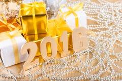 El oro de la composición del Año Nuevo figura 2016 y los regalos en un backg del oro Foto de archivo