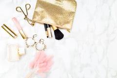 El oro del maquillaje y se ruboriza en el escritorio El oro diseñó el espacio común de la copia Foto de archivo libre de regalías