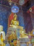 El oro dolió las estatuas de Buda en el templo con la pintura mural Foto de archivo libre de regalías