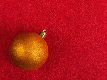 El oro Glittery baublered en fondo glittery imágenes de archivo libres de regalías