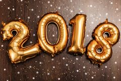 El oro metálico brillante hincha los cuadros 2018, la Navidad, globo del Año Nuevo con las estrellas del brillo en fondo de mader Foto de archivo