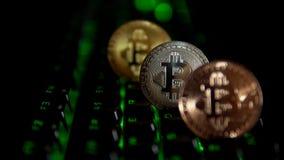 El oro, plata, bronce, bitcoin acuña en el fondo de un teclado que destella metrajes