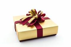 El oro y la caja de regalo marrón con la cinta arquean Fotografía de archivo