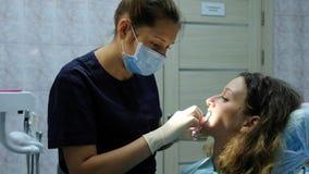 El orthodontist del dentista pone un fixator dental para que una mujer instale un sistema del soporte Visita al dentista foto de archivo