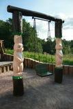 El oscilación del niño extraño con las esculturas de madera Imagenes de archivo
