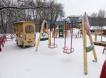 El oscilación en el patio fue cubierto con nieve foto de archivo libre de regalías