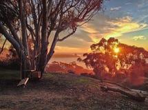 El oscilación fijó con vistas al océano y a la puesta del sol colorida imagen de archivo libre de regalías