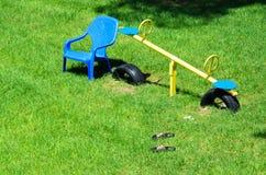 El oscilación y una silla plástica de los niños en la hierba verde Fotografía de archivo