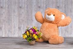 El oso de peluche grande con una cesta de primavera florece imagen de archivo libre de regalías