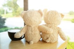 El oso de peluche marrón precioso dos se sienta en el latte de madera de la tabla y del café y mira hacia fuera la ventana de la  imagen de archivo libre de regalías