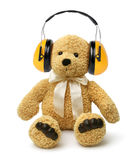 El oso de peluche que se sienta con oye protectores Imagen de archivo