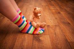 El oso de peluche se sienta en las piernas Imágenes de archivo libres de regalías