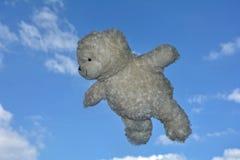 El oso de peluche vuela en el aire con el cielo azul con las nubes Imagen de archivo