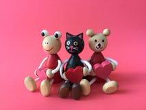 El oso lindo, el gato negro y la rana llevan los juguetes de madera del corazón fotos de archivo