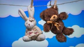 El oso y el conejo de Toy Teddy se suspenden de las pinzas de la cuerda en un fondo de las nubes blancas de la historieta imagenes de archivo