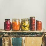 El otoño conservó en vinagre verduras en los tarros colocados en la línea, cosecha cuadrada imágenes de archivo libres de regalías