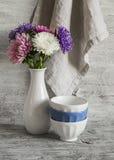 El otoño florece asteres en un florero blanco y un cuenco de cerámica en una superficie de madera ligera imágenes de archivo libres de regalías