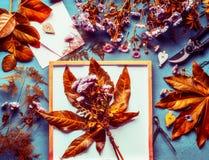 El otoño florece el manojo con las hojas anaranjadas y el crisantemo en fondo de escritorio con las herramientas de la decoración fotografía de archivo libre de regalías