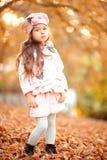 El otoño que lleva de la muchacha linda del niño viste al aire libre Foto de archivo libre de regalías