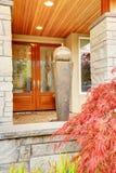 El pórtico de la entrada de la casa con el ajuste de piedra de la columna y de madera de lujo hacen Imágenes de archivo libres de regalías
