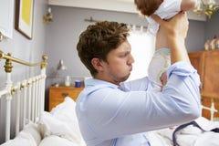 El pañal del bebé cambiante de Dressed For Work del padre en dormitorio Fotos de archivo libres de regalías
