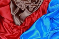 El paño de seda azul y marrón y rojo del satén de dobleces ondulados texturiza vagos Imágenes de archivo libres de regalías
