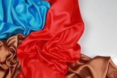 El paño de seda azul y marrón y rojo del satén de dobleces ondulados texturiza vagos Imagenes de archivo