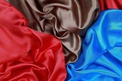 El paño de seda azul y marrón y rojo del satén de dobleces ondulados texturiza vagos Fotografía de archivo