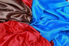 El paño de seda azul y marrón y rojo del satén de dobleces ondulados texturiza vagos Fotos de archivo libres de regalías