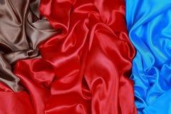 El paño de seda azul y marrón y rojo del satén de dobleces ondulados texturiza vagos Fotografía de archivo libre de regalías