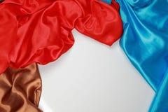 El paño de seda azul y marrón y rojo del satén de dobleces ondulados texturiza vagos Foto de archivo