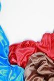 El paño de seda azul y marrón y rojo del satén de dobleces ondulados texturiza vagos Foto de archivo libre de regalías