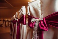 El paño oscuro del rosa y de la leche embellece las sillas cubiertas con la seda beige fotos de archivo