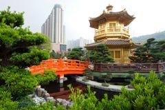 El pabellón de oro y el puente rojo en Nan Lian Garden cerca de la ji Lin Nunnery, Hong Kong Foto de archivo libre de regalías