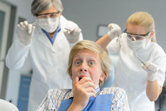 El paciente adolescente asustado asusta el dentista y a la enfermera Fotografía de archivo