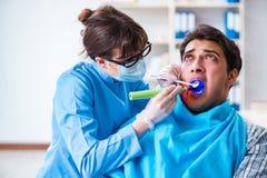 El paciente asustado de dentista durante visita del doctor Fotos de archivo