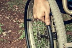 El paciente de la mano del foco selectivo está sosteniendo la rueda de la silla de ruedas en Foto de archivo