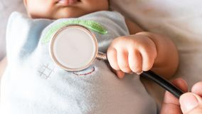 El paciente del bebé tiene fiebre del control con el estetoscopio en hospital imagen de archivo