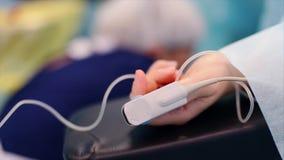 El paciente en la mesa de operaciones Concepto, salvares vidas, la lucha para la vida La mano del paciente con las muestras vital almacen de video