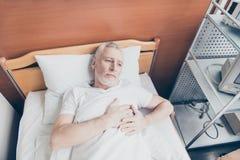 El paciente envejecido está mintiendo en la cama y está llevando a cabo sus manos cerca a h imágenes de archivo libres de regalías