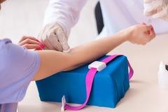 El paciente femenino durante procedimiento de muestreo del an?lisis de sangre imagen de archivo
