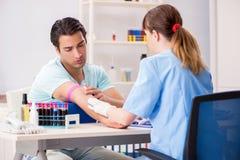 El paciente joven durante procedimiento de muestreo del análisis de sangre imágenes de archivo libres de regalías