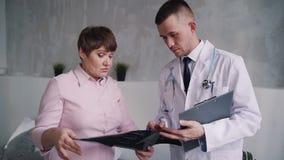 El paciente maduro y el doctor joven es que hablan, de charlas y de discusiones de la investigación médica almacen de metraje de vídeo