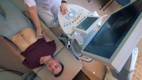 El paciente masculino está consiguiendo su abdomen explorado por la máquina del ultrasonido metrajes