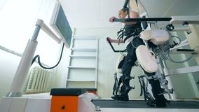 El paciente masculino utiliza la recuperación del equipo para caminar con sus piernas 4K almacen de video