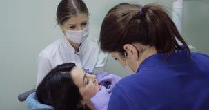 El paciente se sienta en silla del dentista y hace un chequeo, dentista con un control del espejo los dientes y la enfermera se s almacen de video
