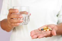 El paciente sostiene un vidrio de agua y de medicina foto de archivo