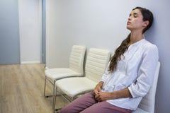 El paciente triste con los ojos cerró sentarse en silla en el hospital fotografía de archivo